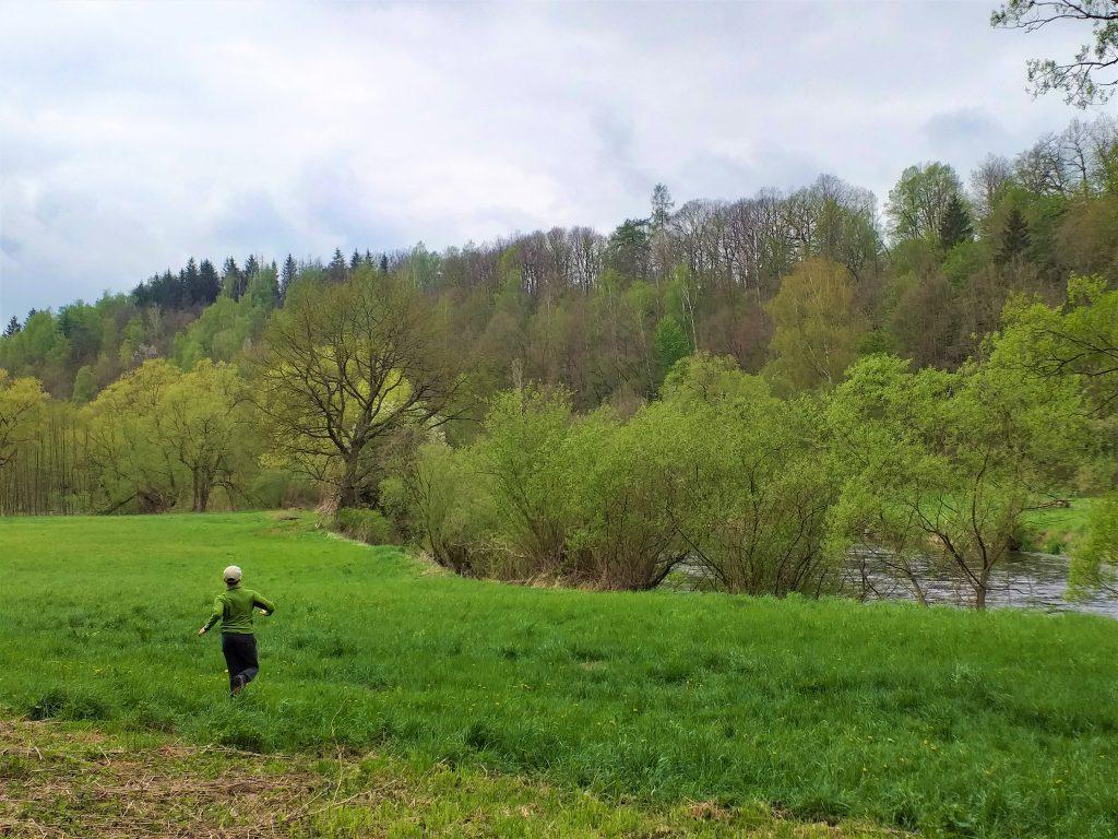 dziecko biegnące przed siebie na łące, po prawej stronie rzeka Bóbr