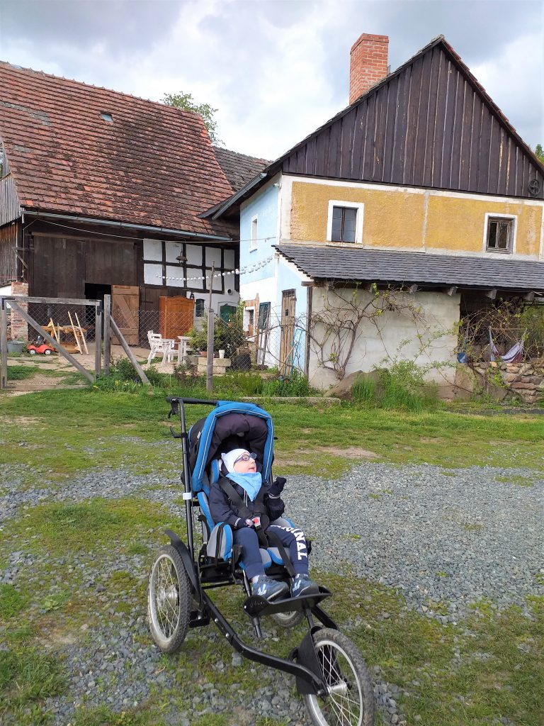 dziecko na cossowym wózku inwalidzkim przez starą kuźnią, Dolina Bobru