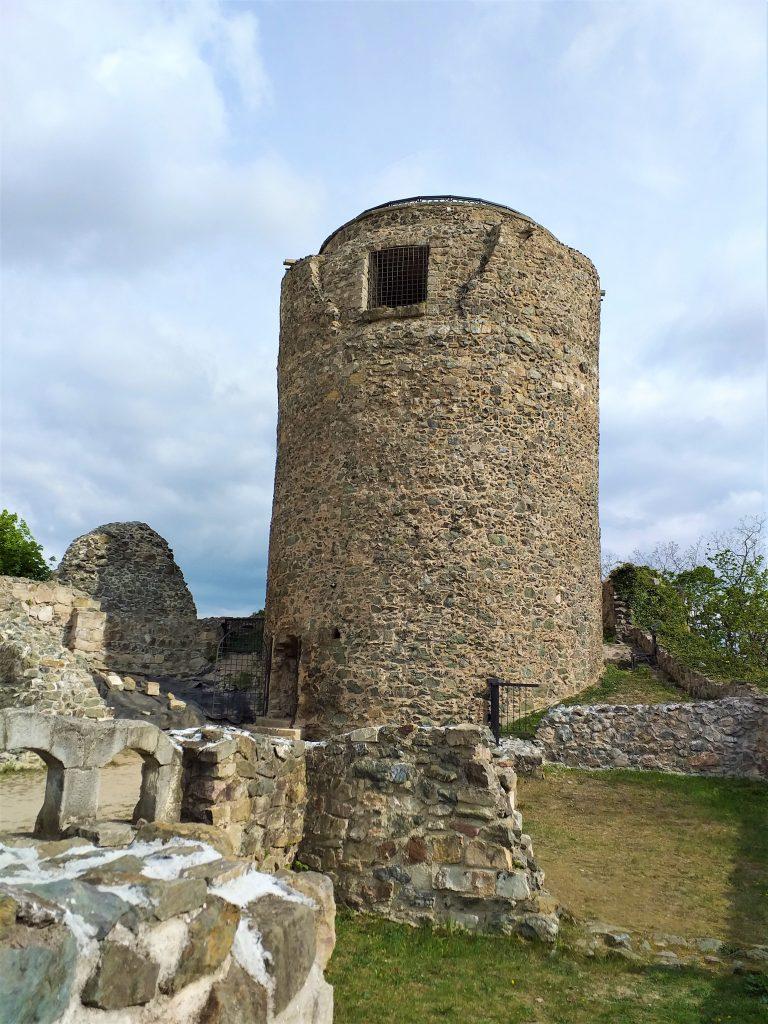 ruiny zamku, w centrum wieża zamkowa, zamek z kamienia, w tle niebieskie niebo
