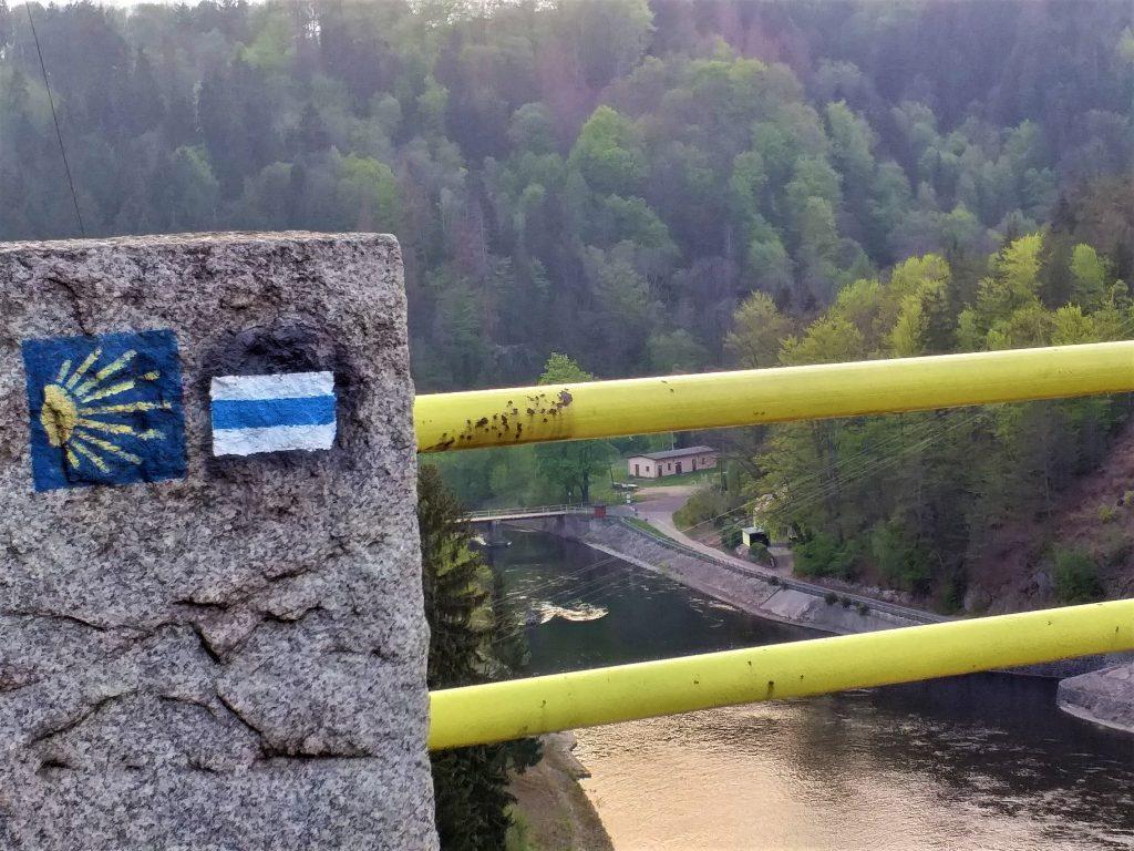 barierka mostu, na kamiennej części namalowany niebieski szlak i szlak świętego Jakuba, widok na rzekę w dole