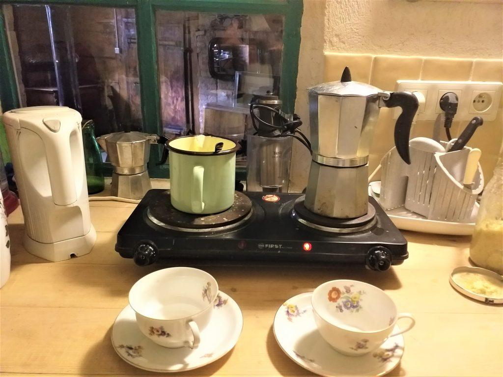 mała kuchenka elektryczna, na niej kawiarka i garnuszek z jedzeniem, przed kuchenką na blacie stoją stare filiżanki w kwiatuszki