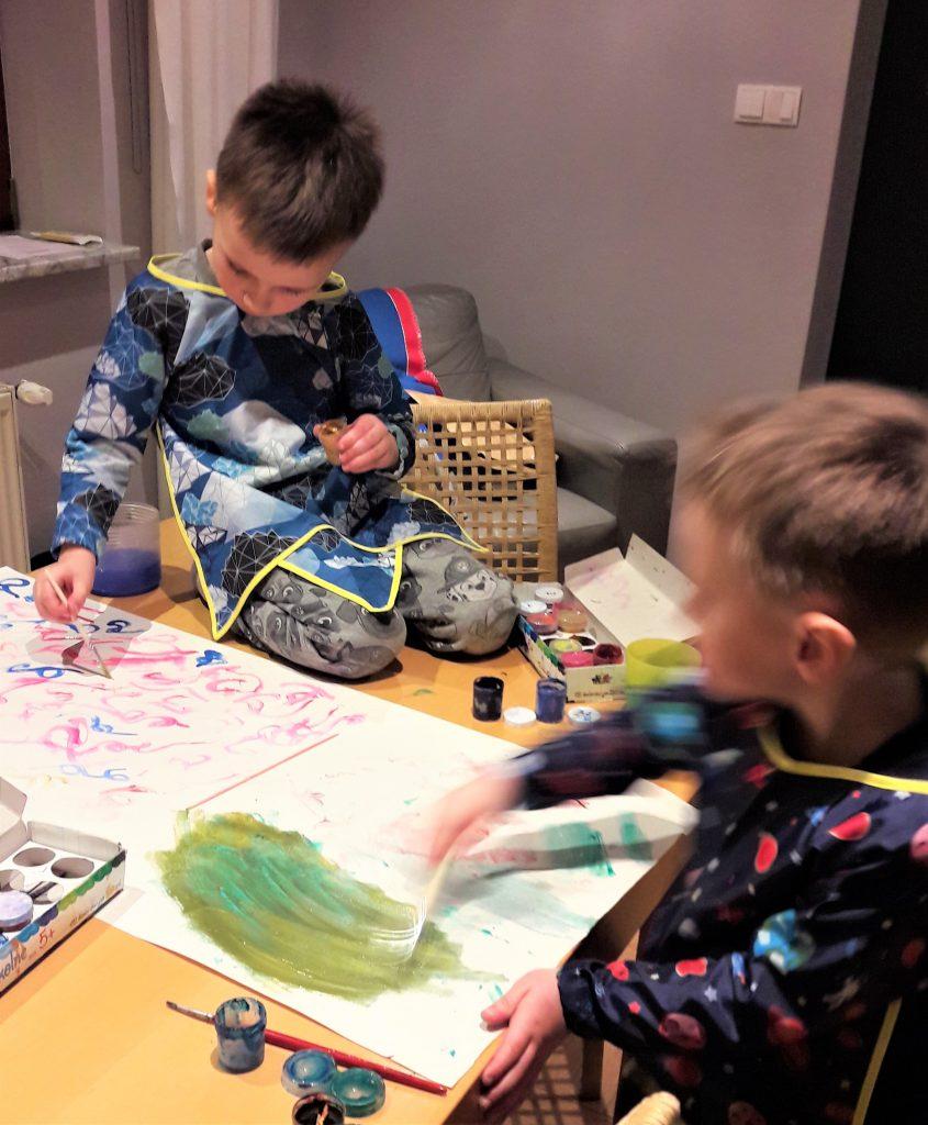 dwóch chłopców maluje coś przy stole