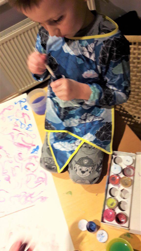 chłopczyk klęczy na stole i maluje farbkami