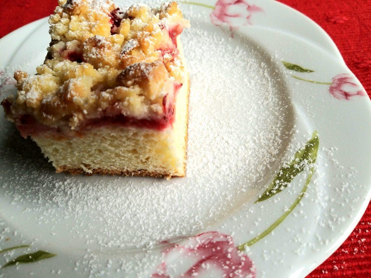 Na białym talerzyku w różowe tulipany lezy kawałek ciasta drożdżowego z truskawkami i kruszonką