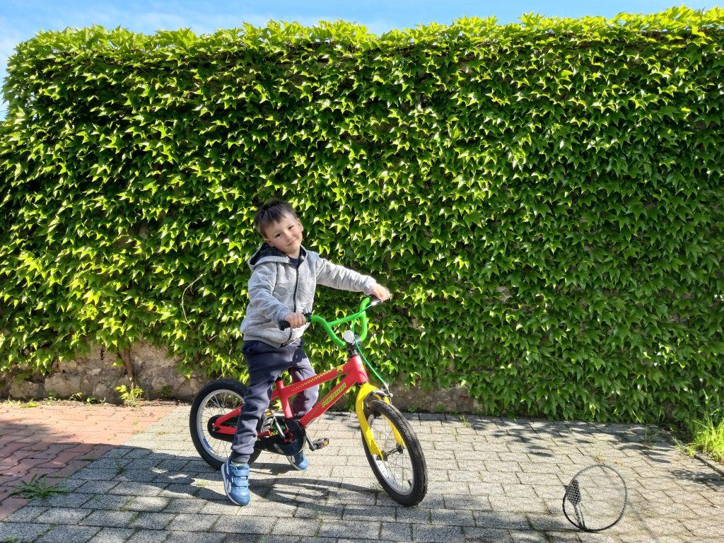 chłopiec siedzi na rowerze, uśmiecha się. W tle ściana zieleni