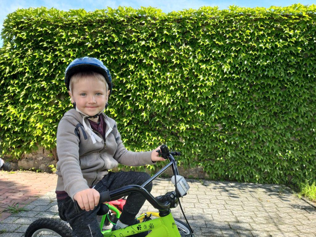chłopiec siedzi na zielonym rowerku, na głowie ma niebieski kask. jest bardzo zadowolony. w tle ściana zieleni