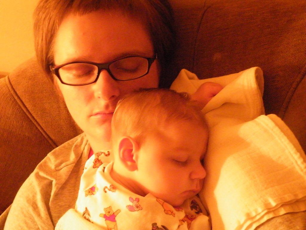 siedząca śpiąca mama ze śpiącym dzieckiem na rekach