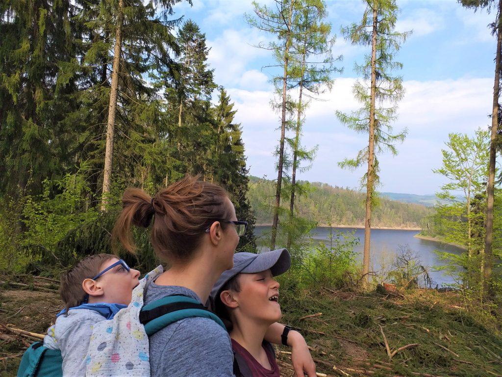 mama z dwójką dzieci w lesie, stoją i patrzą na jezioro, jedno dziecko stoi przed mamą, drugie w nosidle ergonomicznym na jej plecach