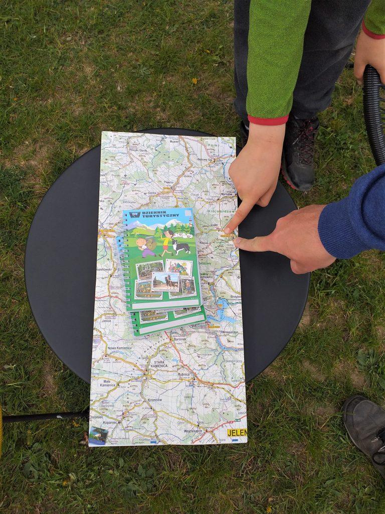 na stoliku lezy mapa, dwa palce wskazują na miejscowość Wleń, na mapie leżą dzienniki turystyczne