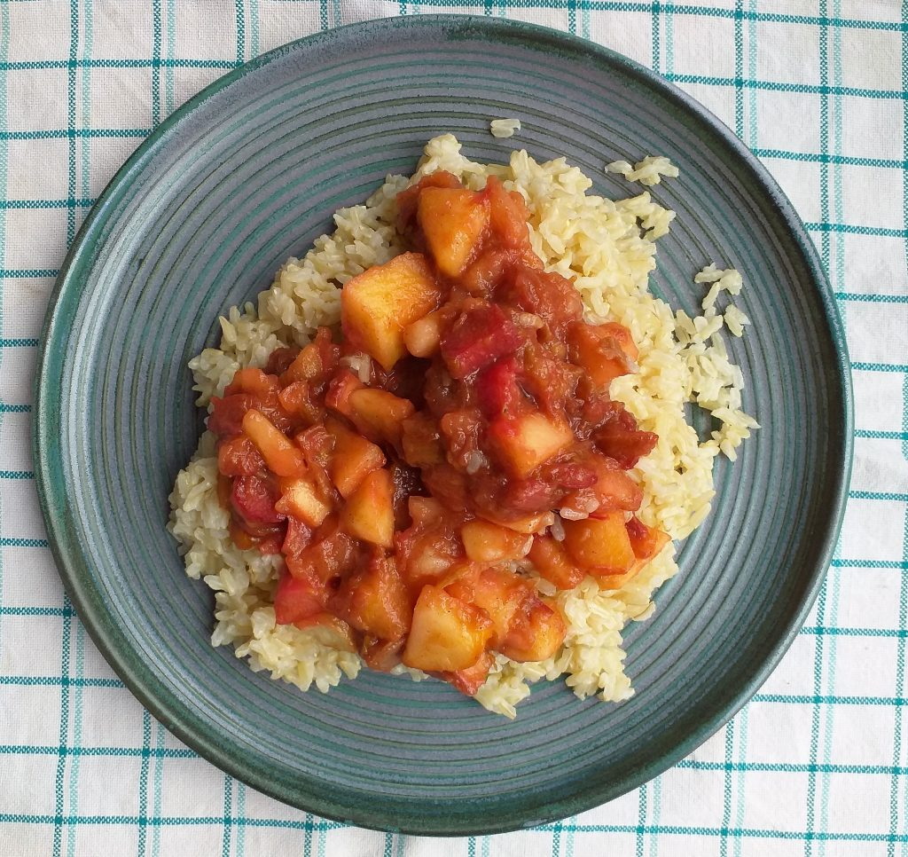 niebieski duży talerz leży na ściereczce. Biała serwetka w turkusową kratkę. Na talerzu ryż. Na ryżu rabarbar i jabłka.