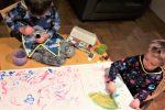 dwóch chłopców ubranych w kolorowe fartuszki maluje farbami