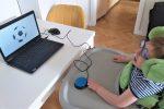 po prawej stronie dziecko w siedzisku, koło lewej reki switch, po lewej stronie na stole laptop. na laptopie prezentacja o piłce nożnej
